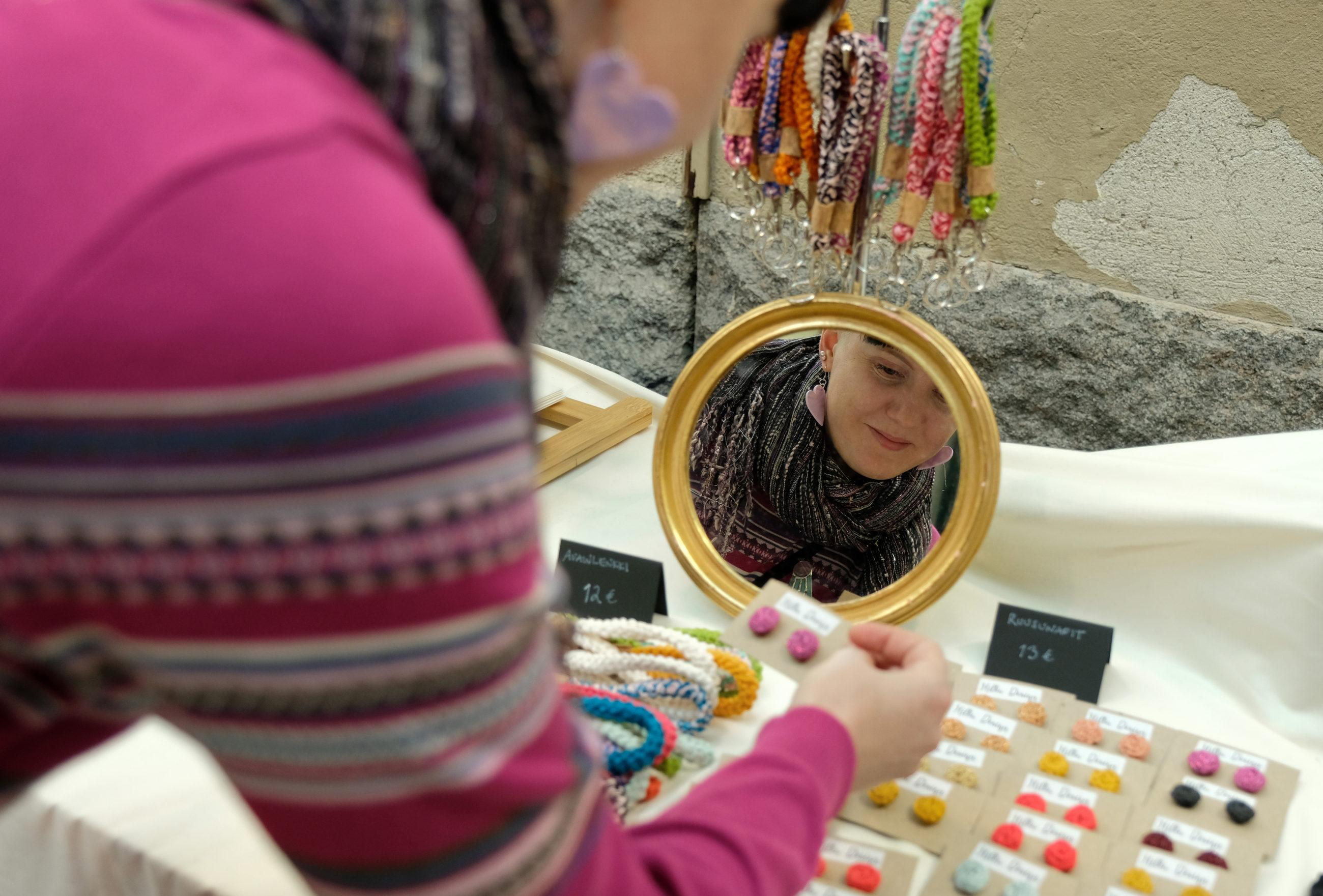 Kirjavaan paitaan pukeutunut henkilö asettelee pöydälle korvakoruja myyntiin, henkilön kasvot näkyvät pöydällä olevasta peilistä.