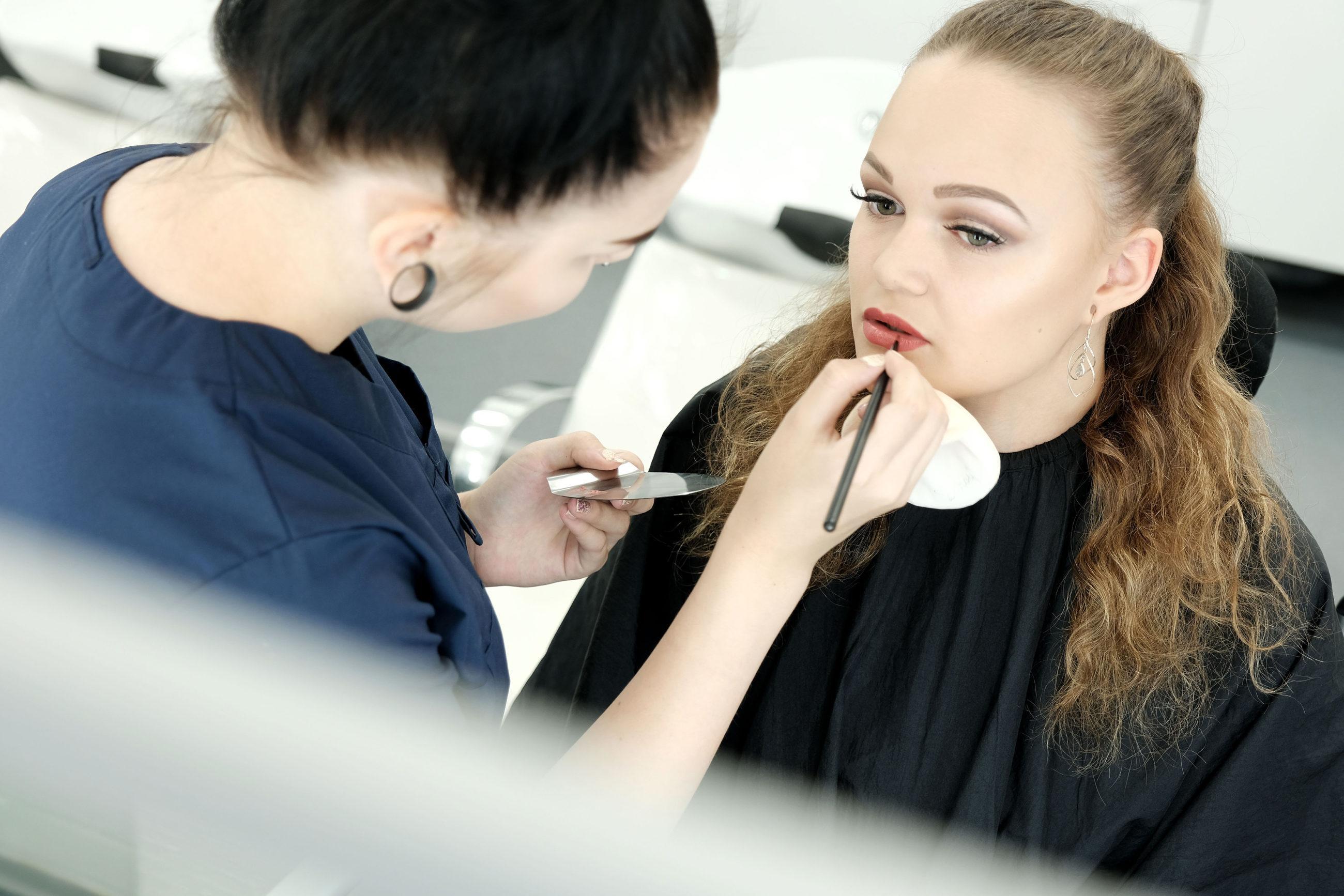 Siniseen kosmetologin työasuun pukeutunut henkilö laittaa siveltimellä huulipunaa nuorelle naiselle.