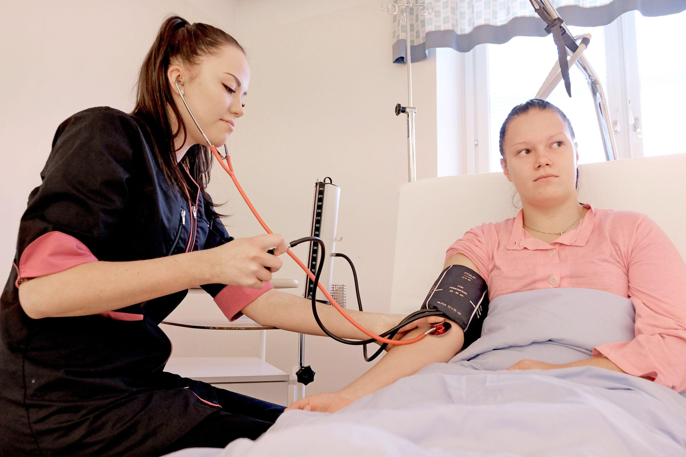 Henkilö mittaa verenpainetta toiselta henkilöltä, joka on sairaalasängyssä.