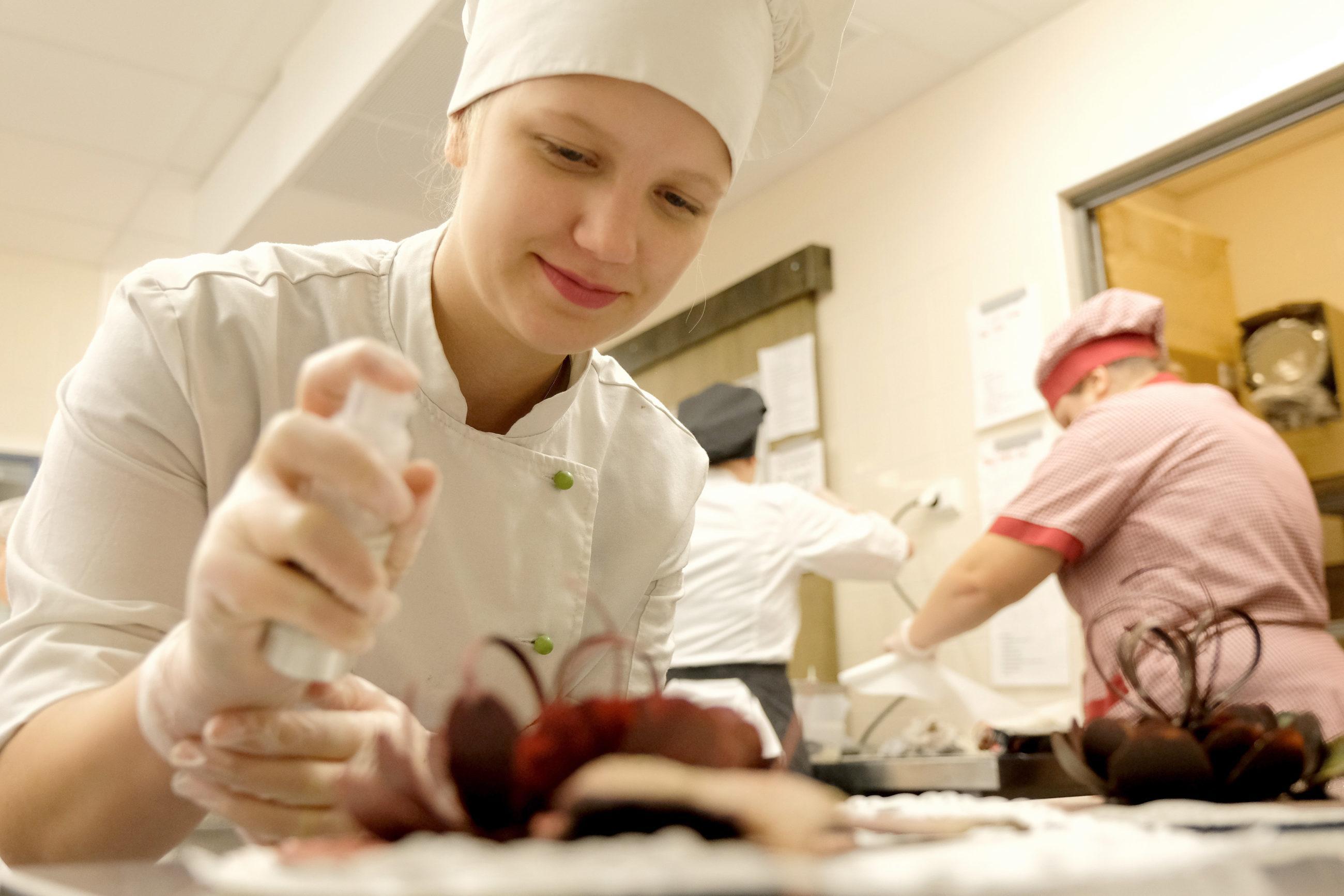 Valkoiseen kokinasuun pukeutunut henkilö koristelee pöydällä olevia leivoksia, taustalla näkyy kaksi muuta keittiötyöasuun pukeutunutta henkilöä.