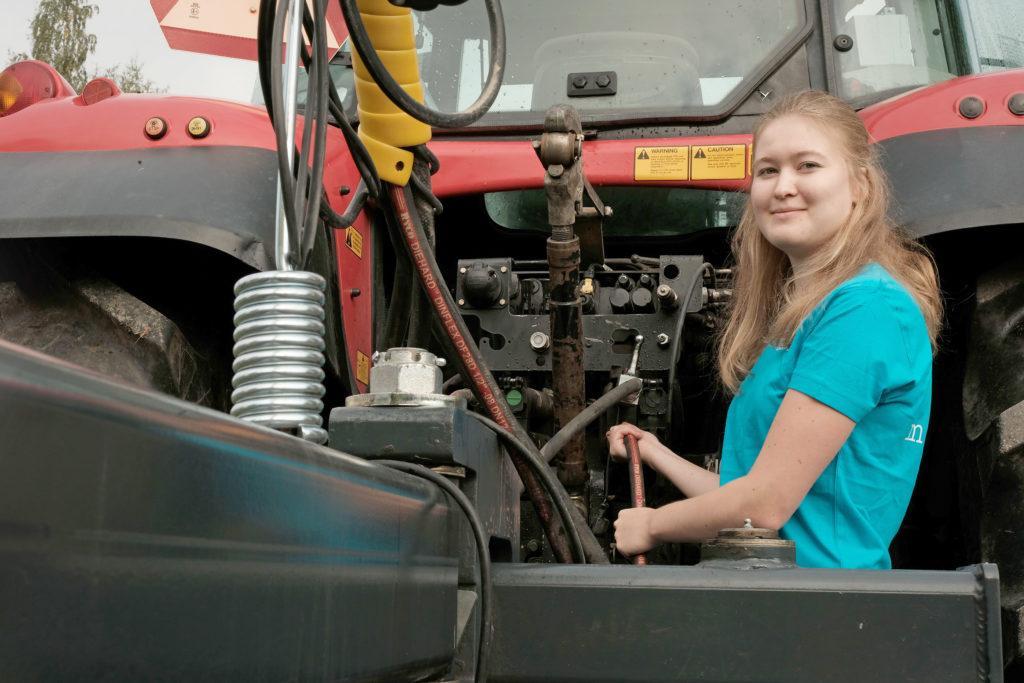 Henkilö työskentelee traktorin laitteiston parissa.