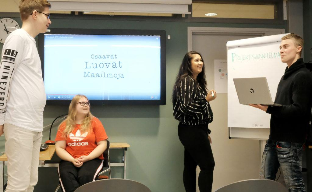 Kaksi naista ja kaksi miestä luokkahuoneessa, seinällä tv-ruutu, jossa on teksti Osaavat luovat maailmoja, henkilöt hymyilevät, yhdellä henkilöllä on kädessään kannettava tietokone.