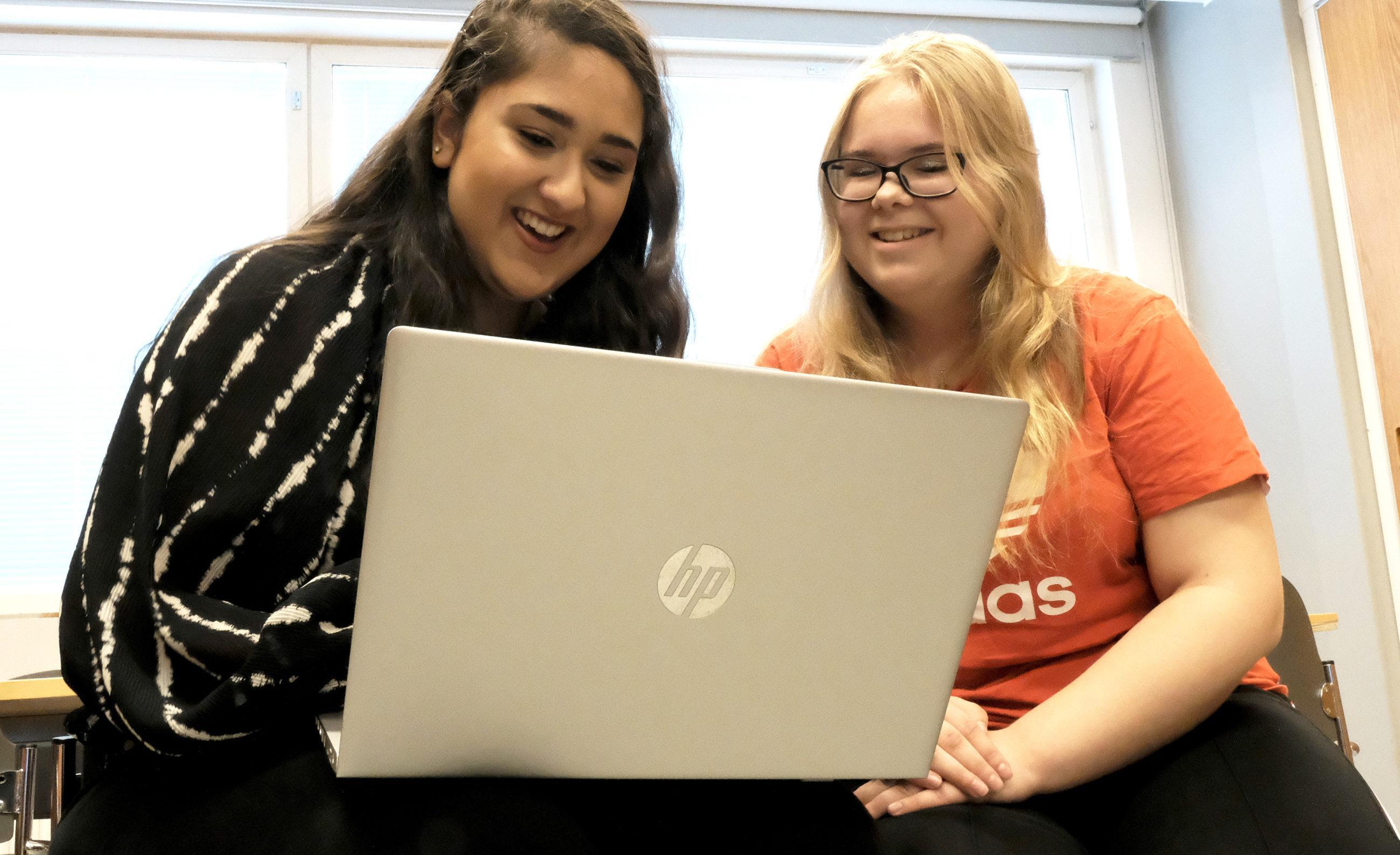 Kaksi henkilöä naista katsoo yhdessä kannettavan tietokoneen näyttöä.