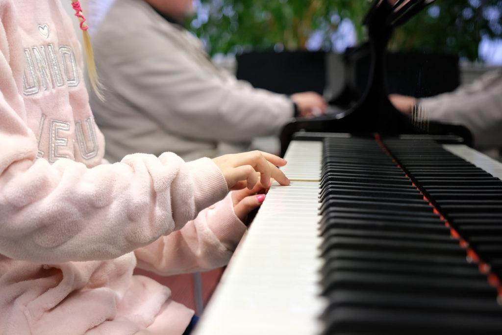Etualalla lapsen kädet pianon koskettimilla, taustalla näkyy toisen henkilön kädet toisen pianon koskettimilla.