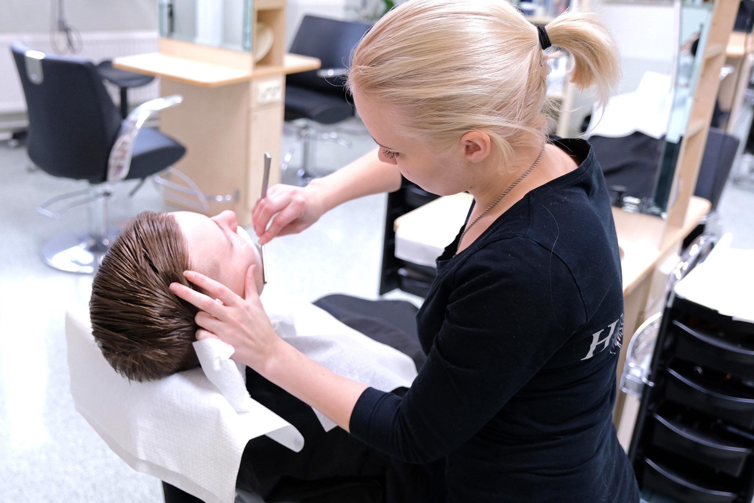 Nainen leikkaa parturituolissa istuvan miehen partaa partaveitsellä, taustalla näkyy lisää parturituoleja.