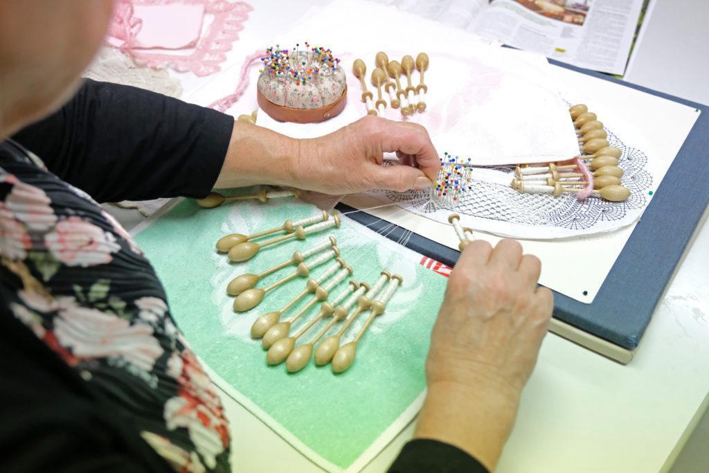 Henkilö tekee nypläystyötä, nypäläyksessä käytettäviä välineitä ja kuvio, jonka mukaan työtä tehdään.