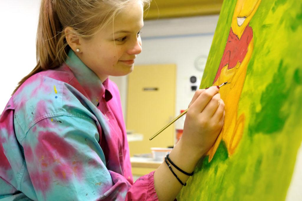 Henkilö maalaa taulua, hänellä on päällään pinkki-turkoosikirjava paita, taulussa on vihreää, punaista ja keltaista.