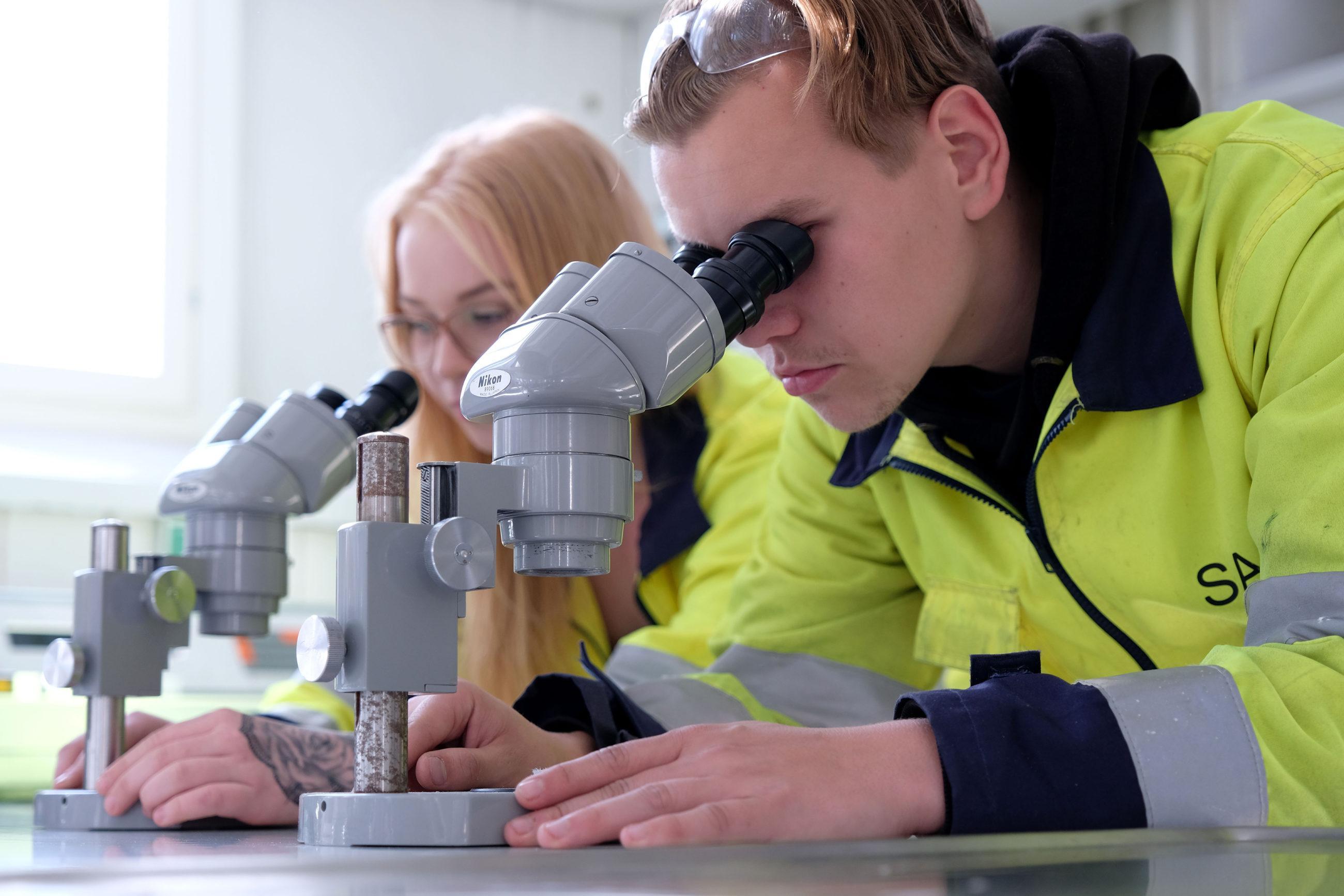 Kaksi henkilöä tutkii jotain mikroskoopeilla, kummallakin yllään kelta-mustat työvaatteet.