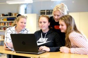 Neljä henkilöä katsoo yhdessä kannettavan tietokoneen ruutua.