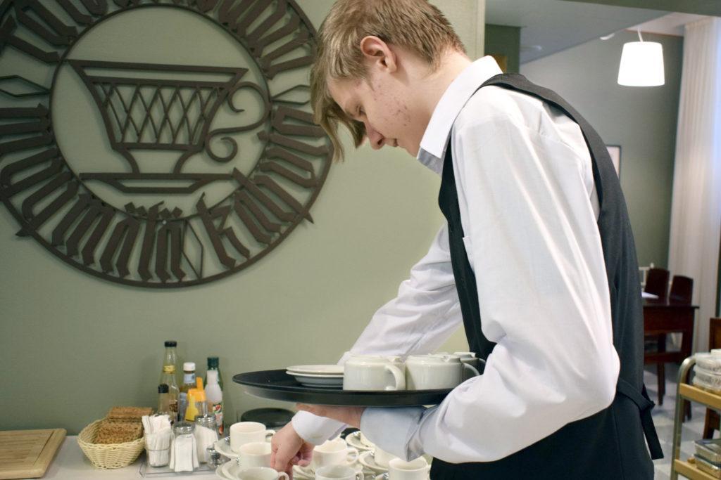 Nuori mieshenkilö kantaa tarjotinta, josta hän kattaa pöytään kahvikuppeja ja-lautasia, hän on pukeutunut valkoiseen paitaan ja mustaan liiviin, taustalla seinällä metallinen taideteos, jossa tekstiä ja tyylitelty kahvikupin kuva.