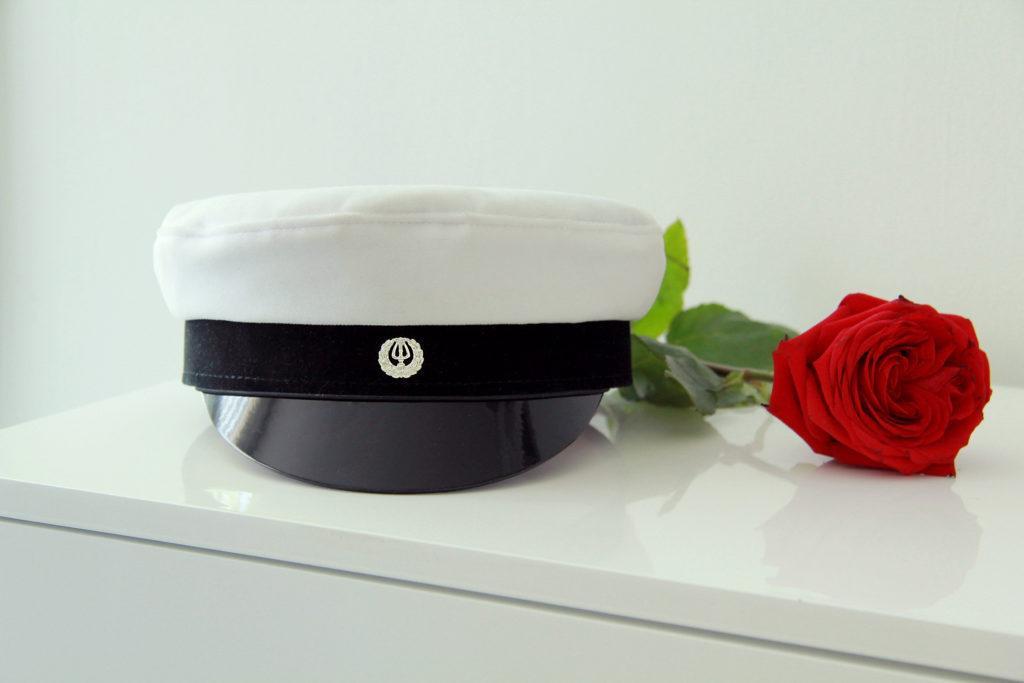 Ylioppilaslakki ja punainen ruusu valkoisen tason päällä. valkoista taustaa vasten.