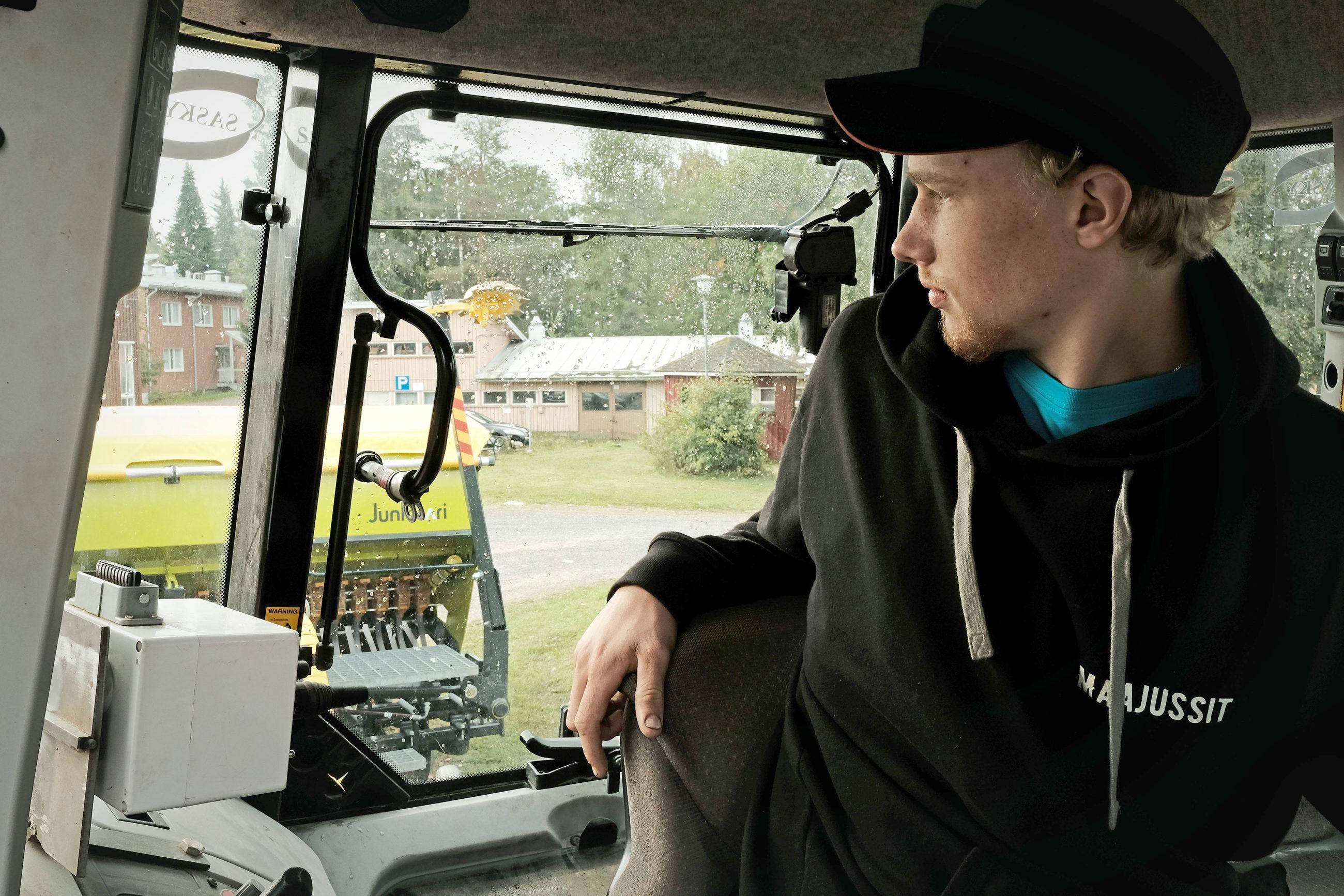 Lippalakkipäinen mies traktorin ohjaamossa, taustalla näkyy rakennuksia, mihen paidassa teksti: Maajussit.