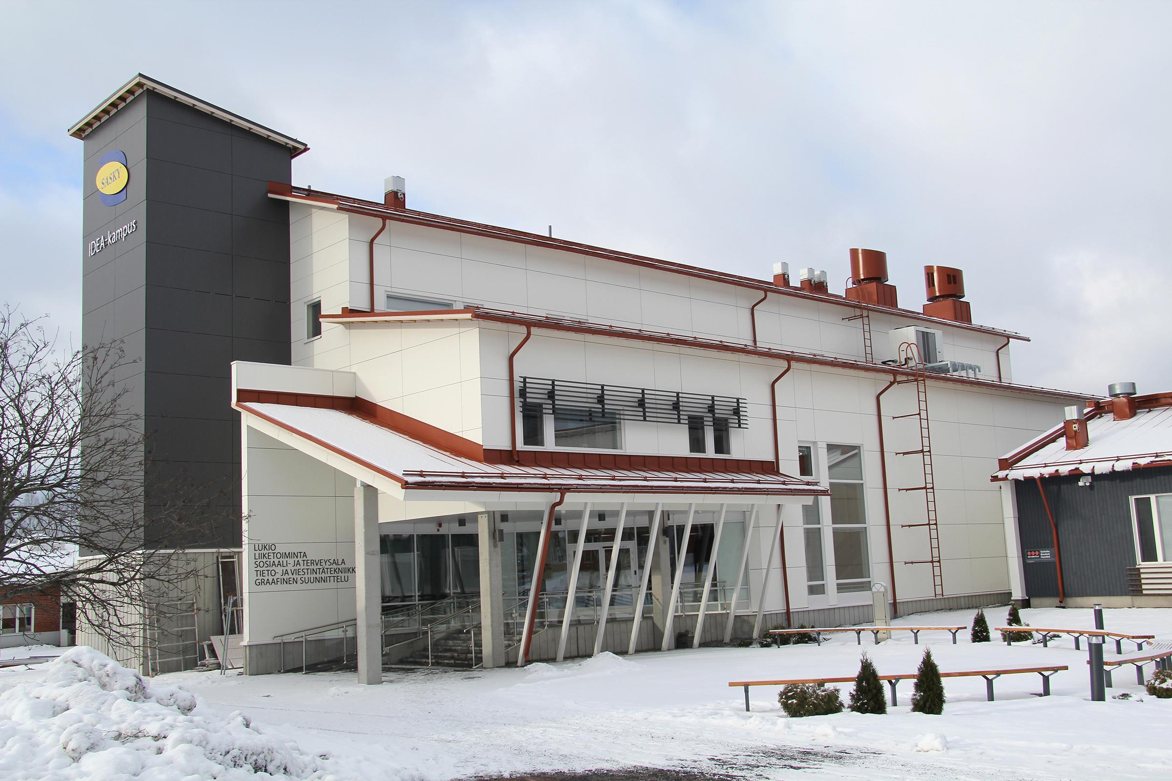 Valkoinen moderni koulurakennus, jossa vasemmalla reunalla harmaa tornimainen rakennelma, jonka seinässä sini-keltainen logo, Saskyn IDEA-kampus uudisrakennus Ikaalisissa.