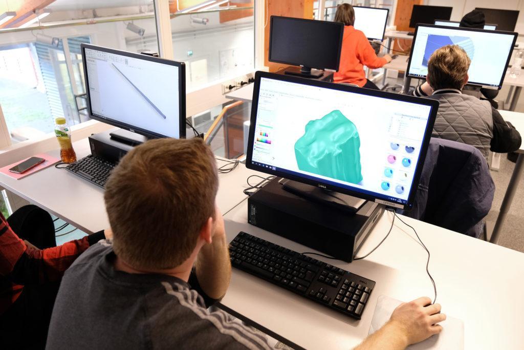 Ihmisiä tietokoneluokassa, tietkoneen ruudulla näkyy 3D-mallinnusohjelmalla työskentelyä.