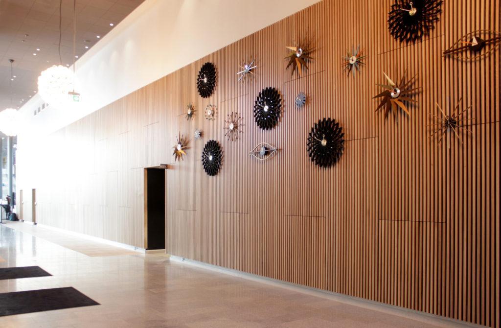 Iso tila, jossa puupaneelilla verhoiltu seinä, seinällä erimallisia kelloja.