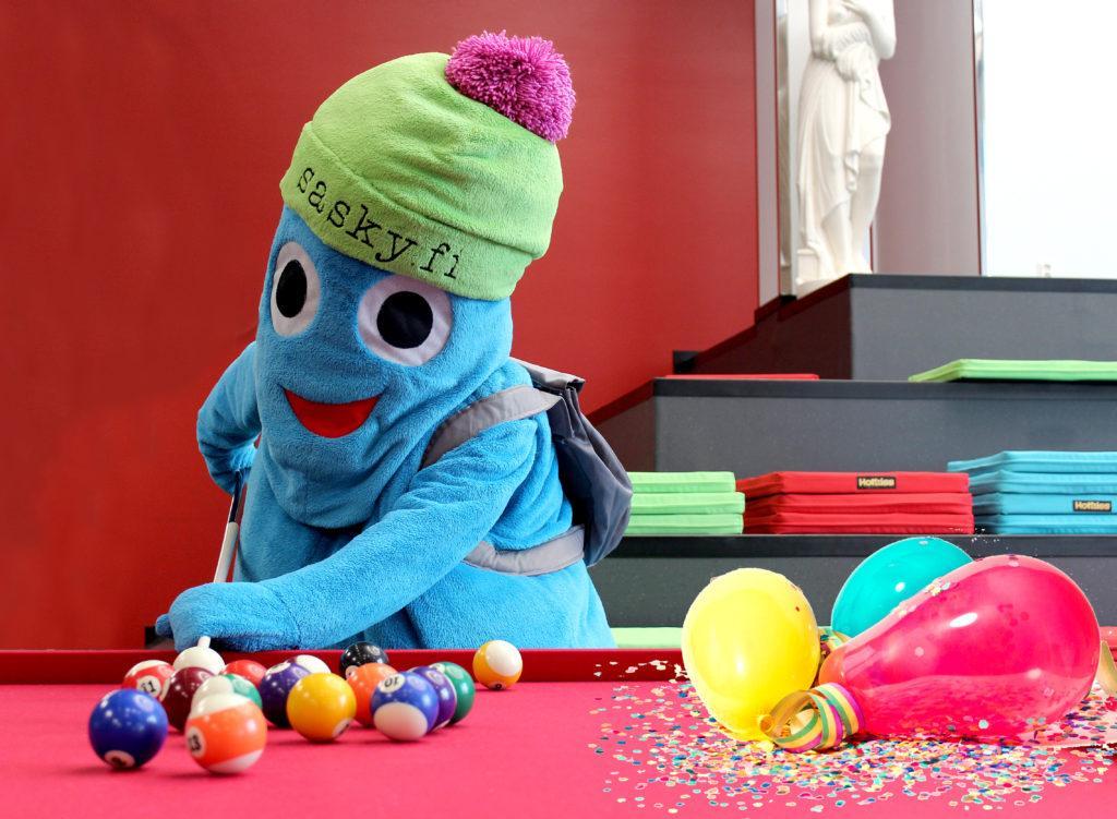 Turkoosi maskottihahmo pelaa biljardia, hahmolla vihreä pipo, jossa pinkki tupsu ja teksti sasky.fi, biljardipöydällä biljardipalloja ja ilmapalloja.