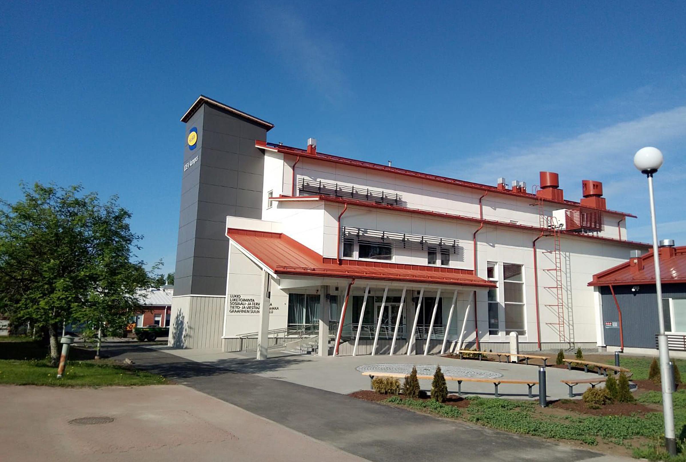 Valkoinen moderni koulurakennus, jossa vasemmalla reunalla harmaa tornimainen rakennelma, jonka seinässä sini-keltainen logo, Saskyn IDEA-kampus uudisrakennus Ikaalisissa, kesäinen kuva.