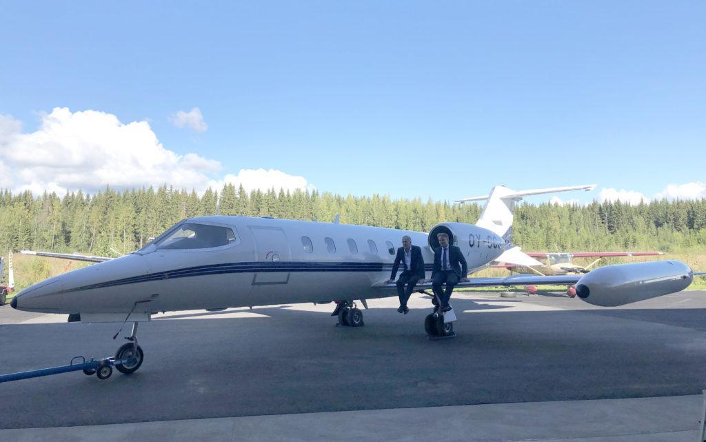 Lentokone, jonka siiven päällä istuu kaksi miestä.