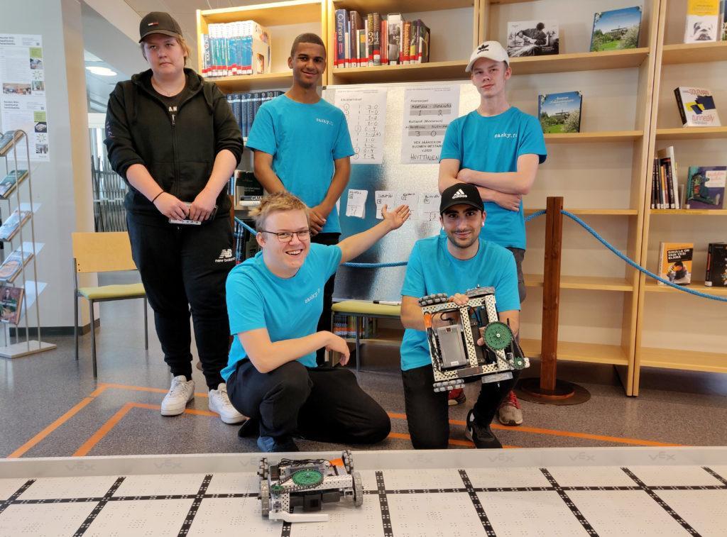 Viisi henkilöä josta neljällä päällä turkoosit t-paidat, yhdellä kädessään kauko-ohjattava robotti, yksi robotti kuvassa etualalla lattialla.