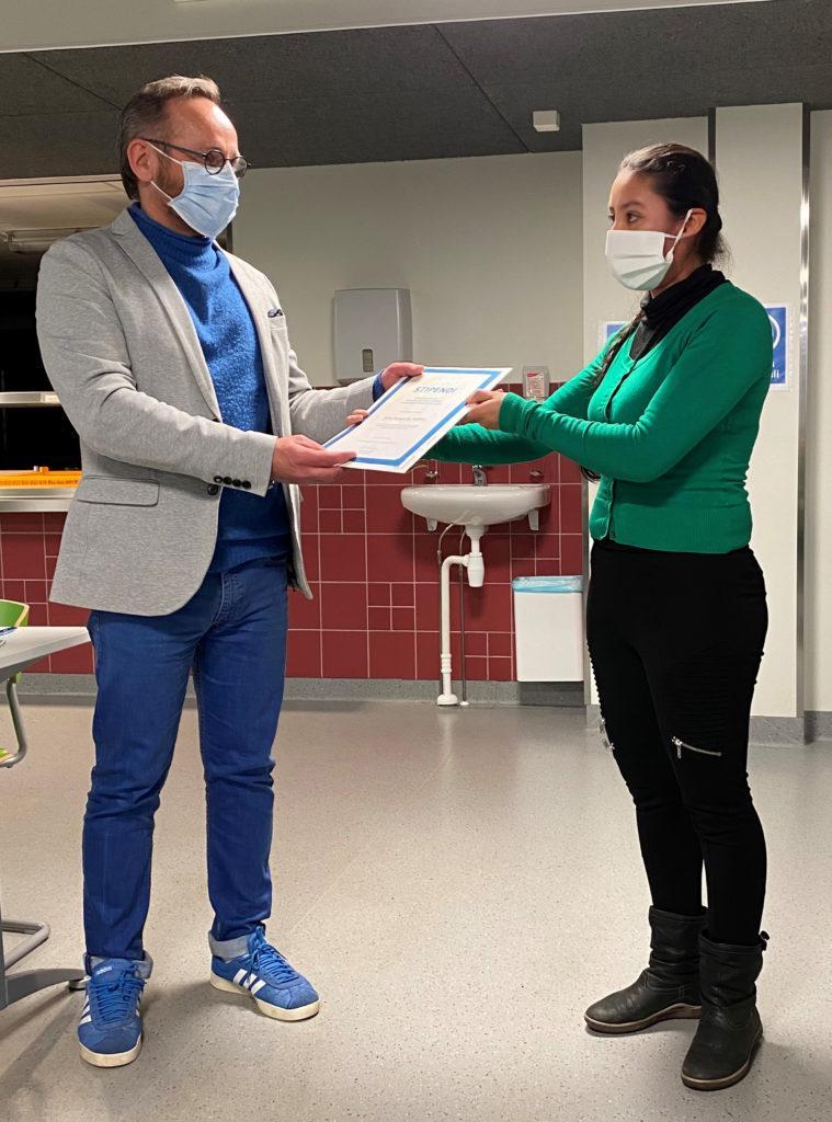 Kaksi henkilöä maskit kasvoillaan, toinen luovuttaa toiselle kunniakirjan.