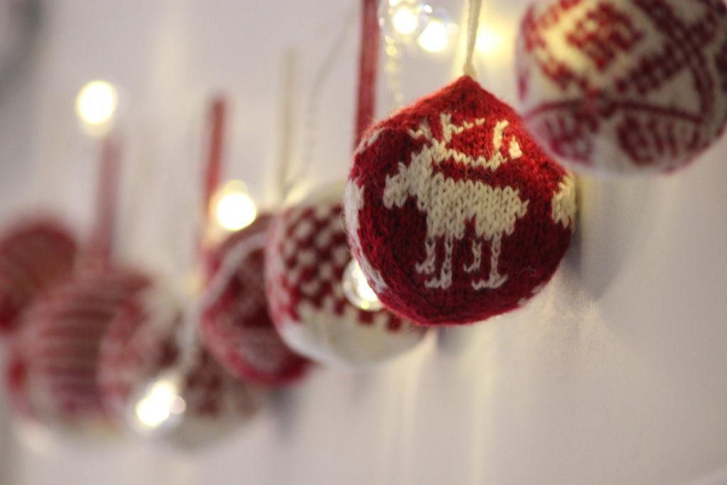 Punavalkoisia neulottuja joulupalloja ja jouluvaloja.