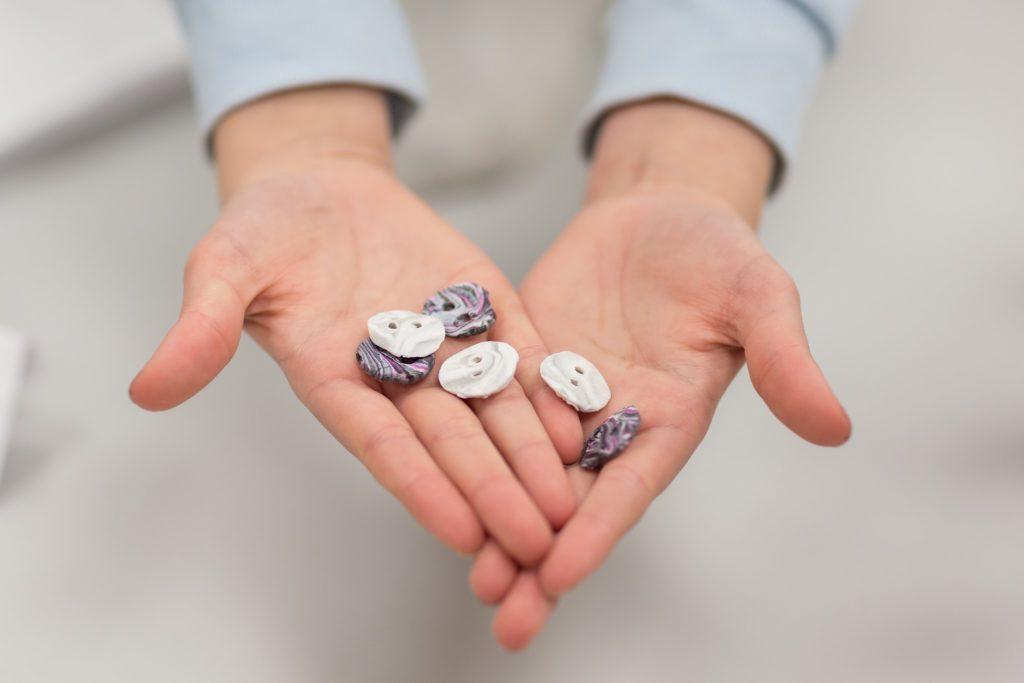 Kädet, joiden päällä erivärisiä nappeja.