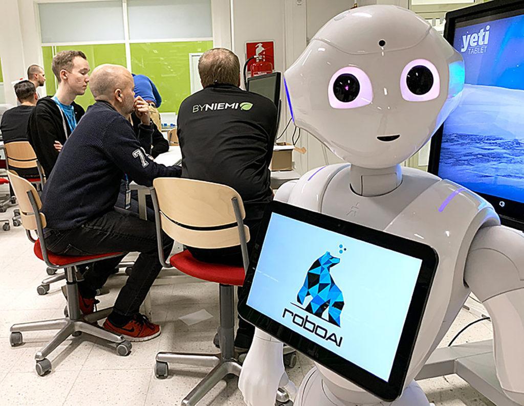 Etuallalla robotti, jonka näyttöruudussa teksti roboai, taustalla henkilöitä tietokoneen ääressä.