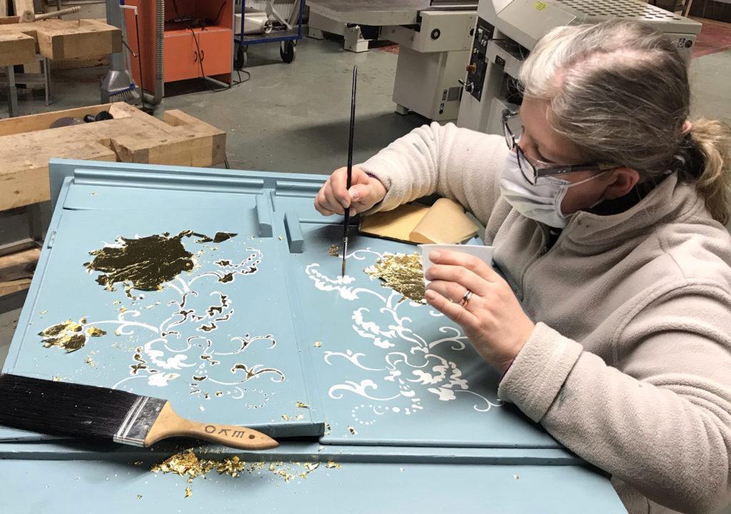 Henkilö tekee kultauskoristeita vaaleansinisen kaapin oviin.