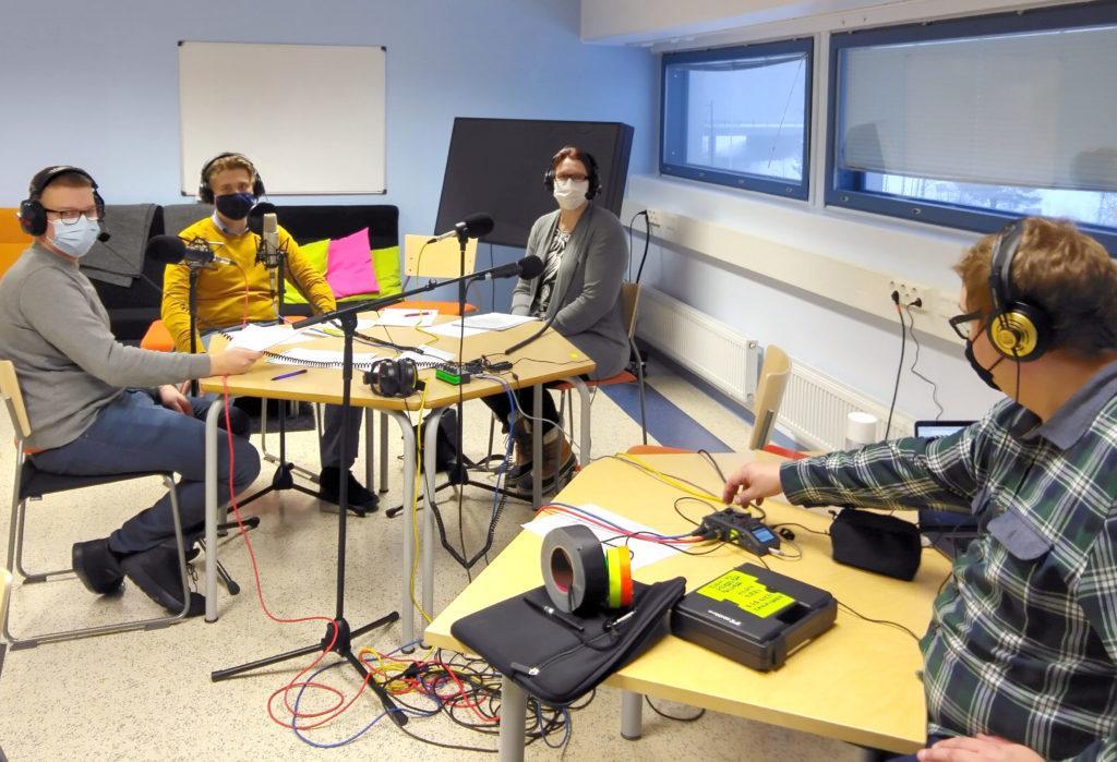 Neljä henkilöä kuulokkeet päässä nauhoittamassa podcastia.