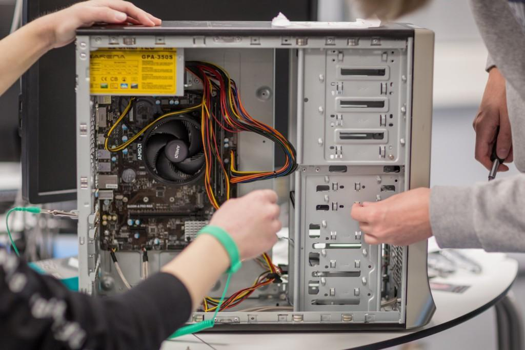 Kaksi henkilöä työskentelee avatun tietokoneen äärellä.