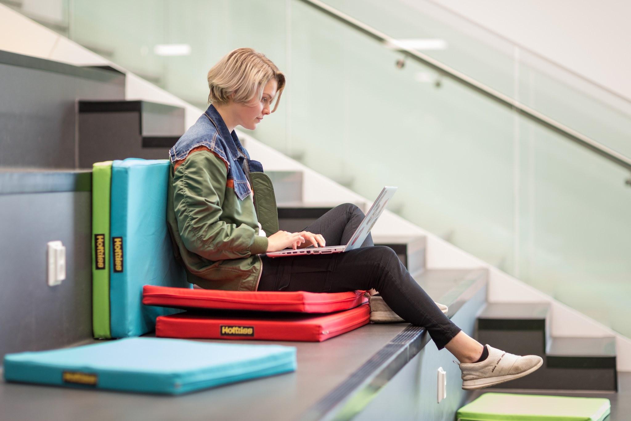 Tyttö istuuu portailla ja tekee töitä kannettavalla tietokoneella.