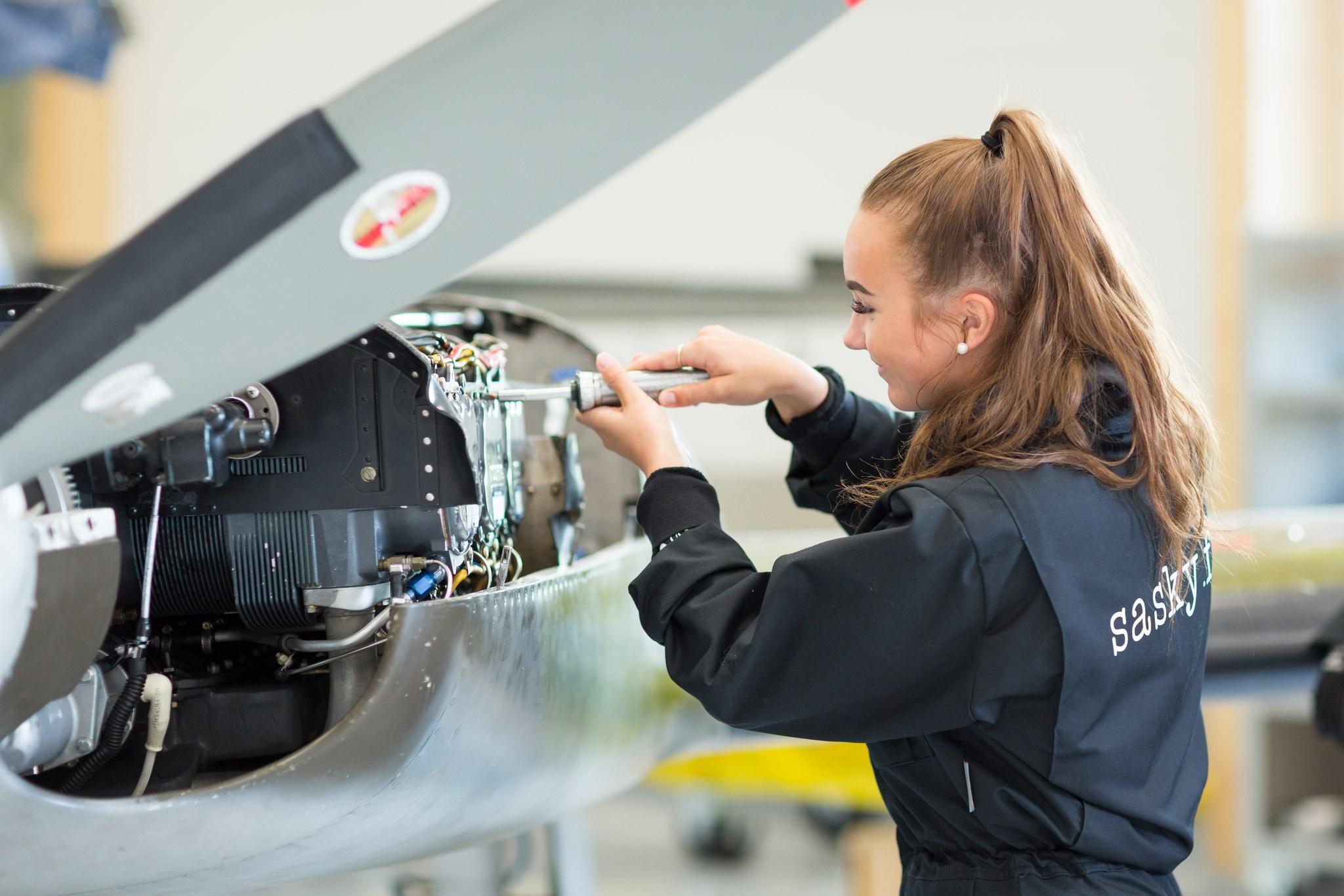Nainen huoltaa lentokonetta.