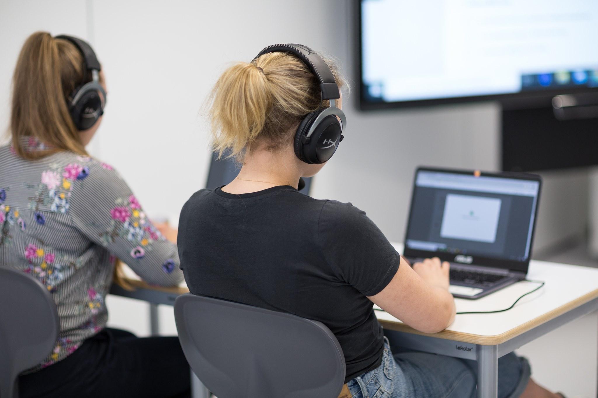 Kaksi henkilöä istuu tietokoneen ääressä kuulokkeet päässä.