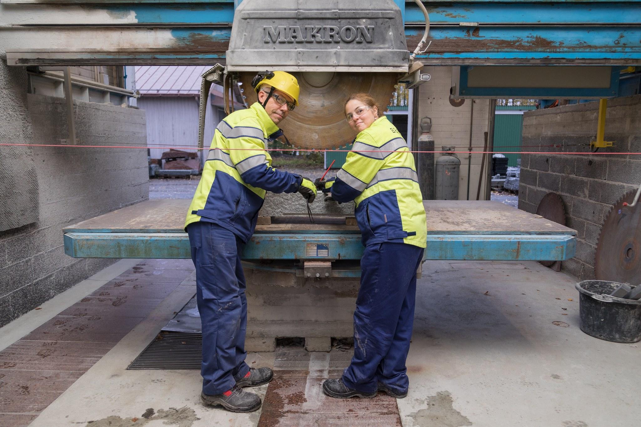 Mies ja nainen työvaatteissa kiventyöstökoneen edessä.