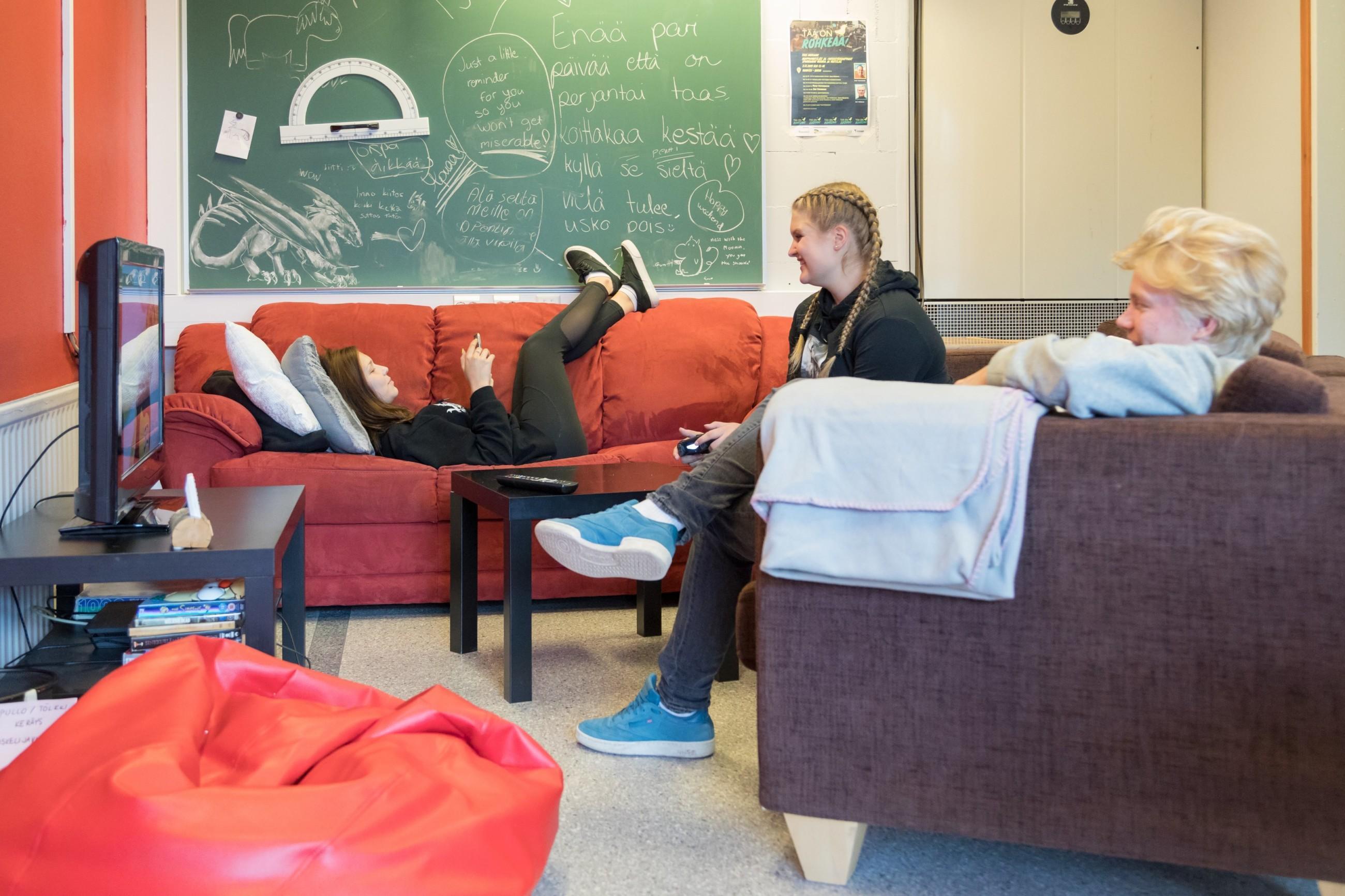 Kolme opiskelijaa löhöilemässä taukotilan sohvilla iloisina.