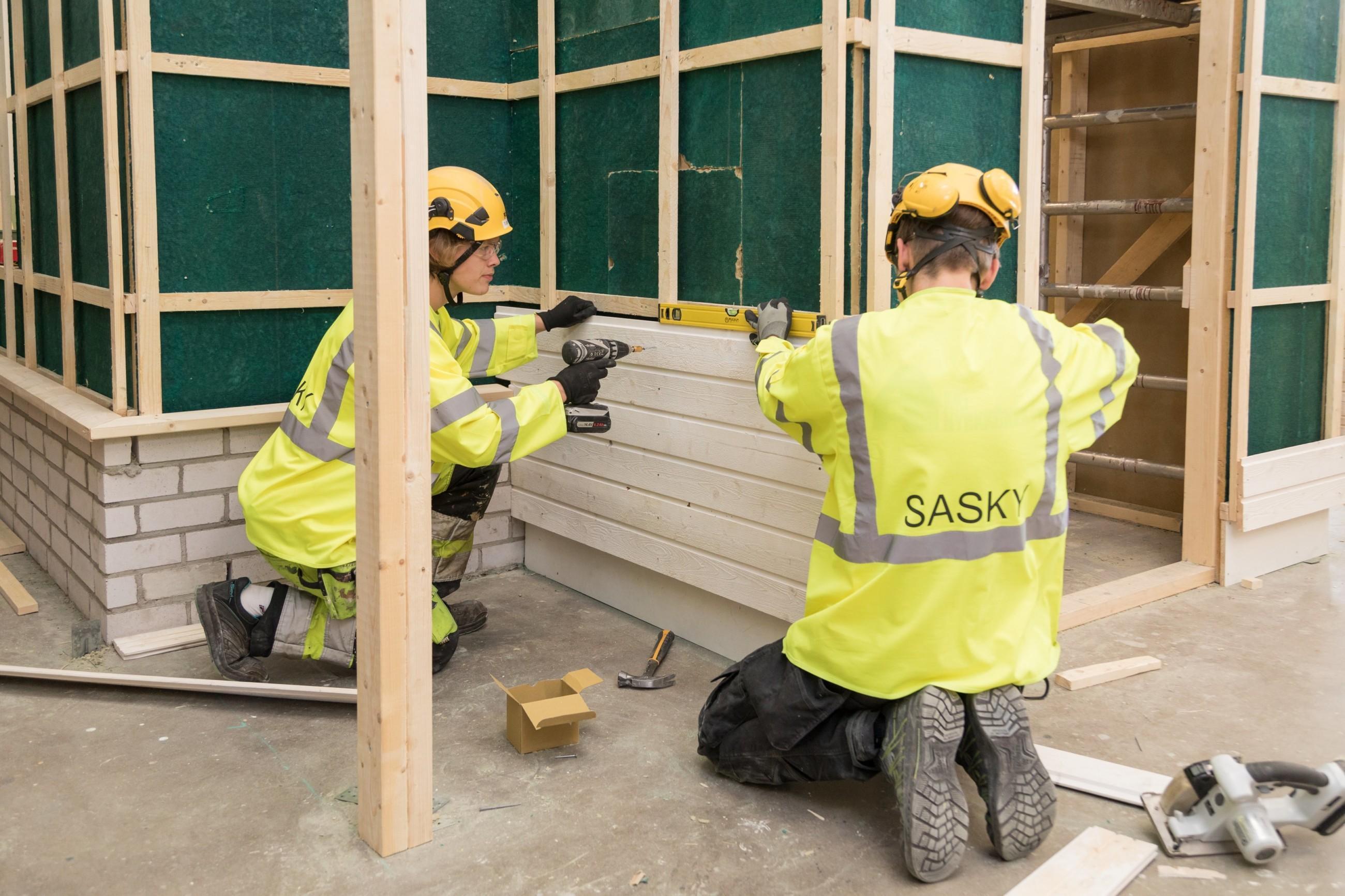 Kaksi henkilöä asentaa seinään puupaneleita ja tarkistavat suoruuden vatupassilla.
