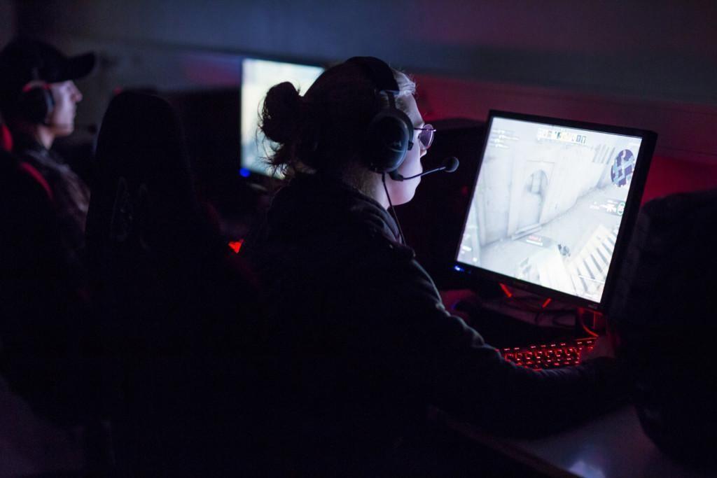 Henkilö pelaa tietokoneella, henkilöllä on päässä kuulokkeet, joissa kiinni sankamikrofoni.