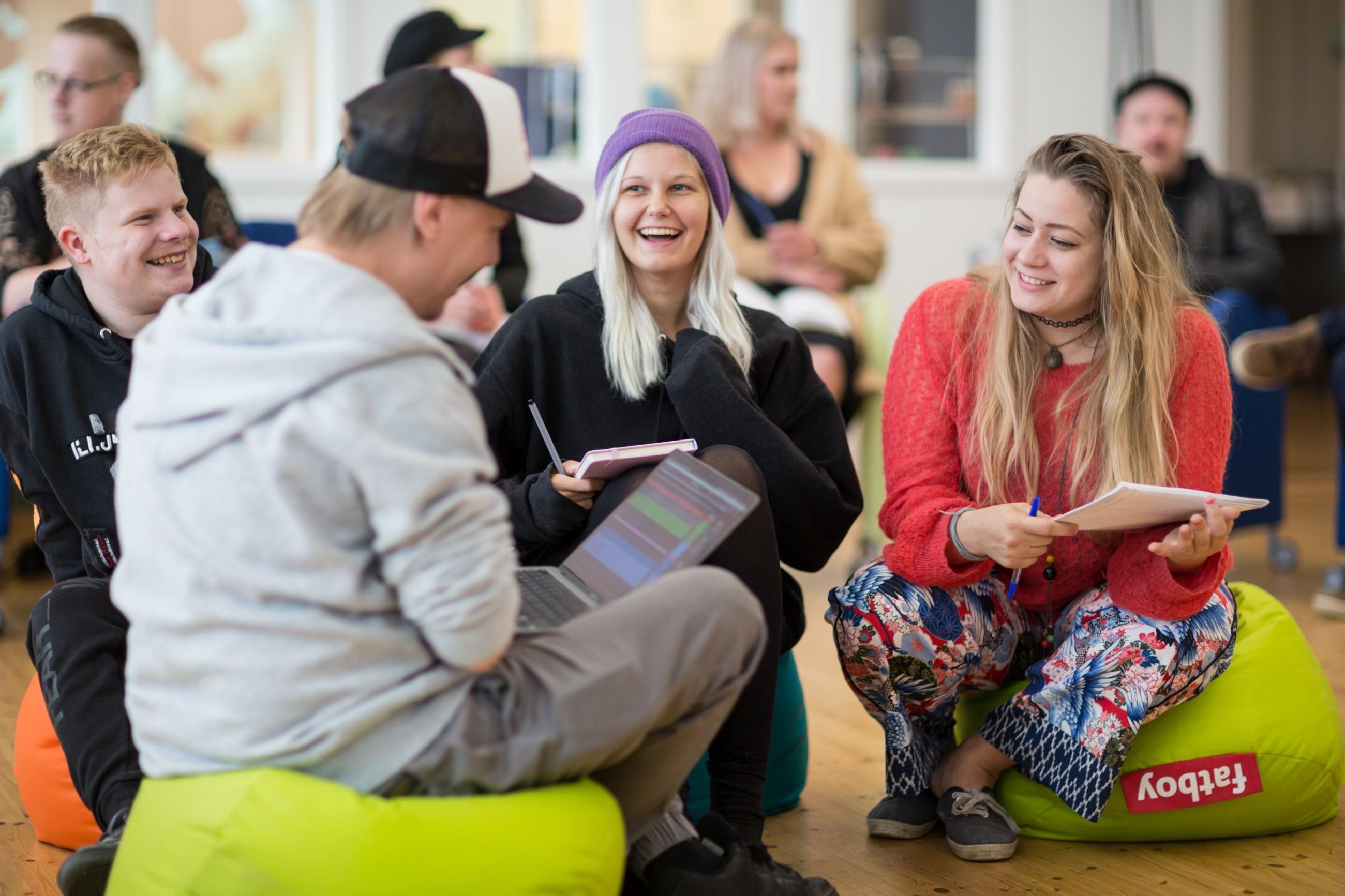 Neljä iloista opiskelijaa istuu säkkituoleilla, taustalla näkyy lisää opiskelijoita.