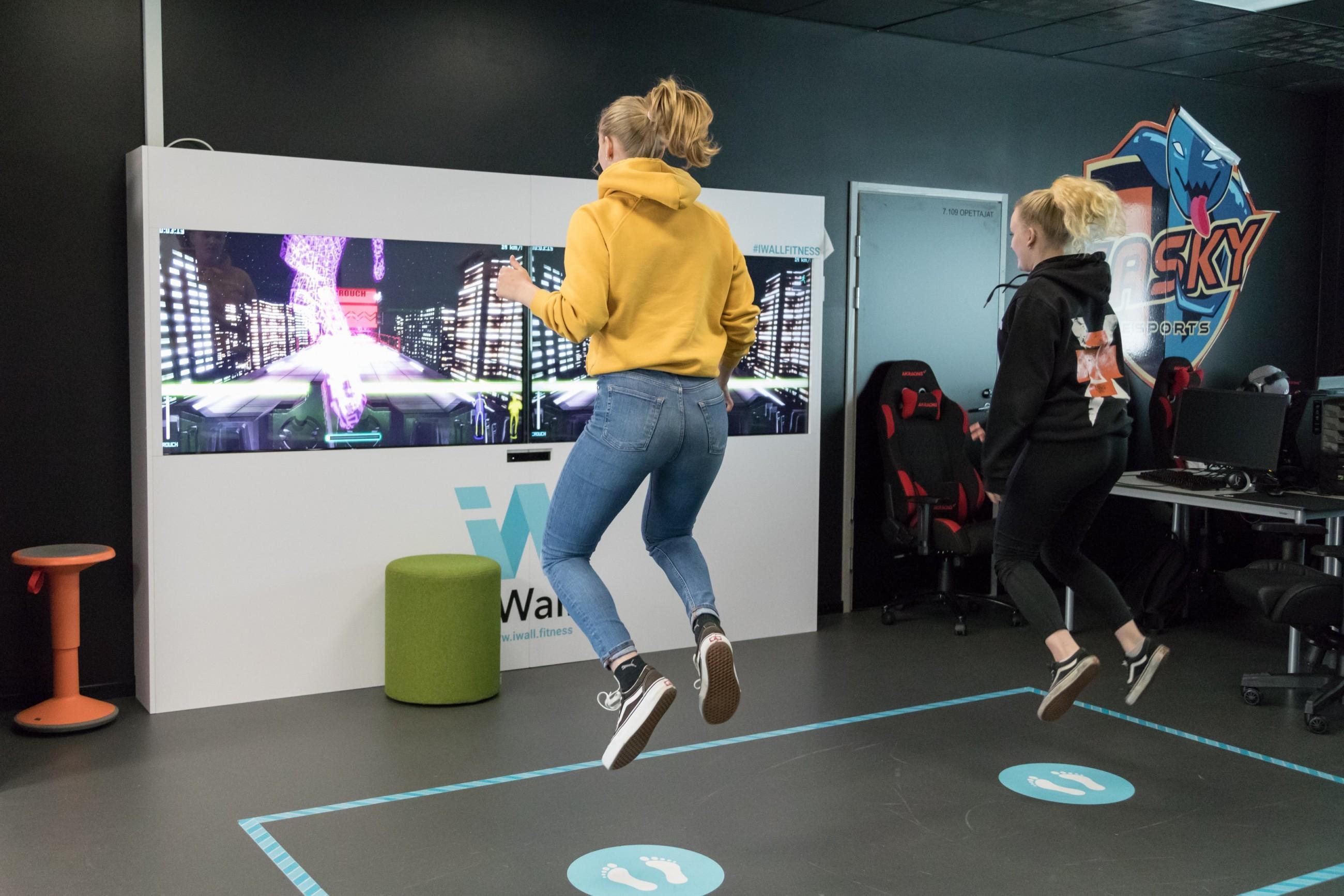 Kaksi henkilöä pelaa iWall peliä ja hyppäävät korkealle.