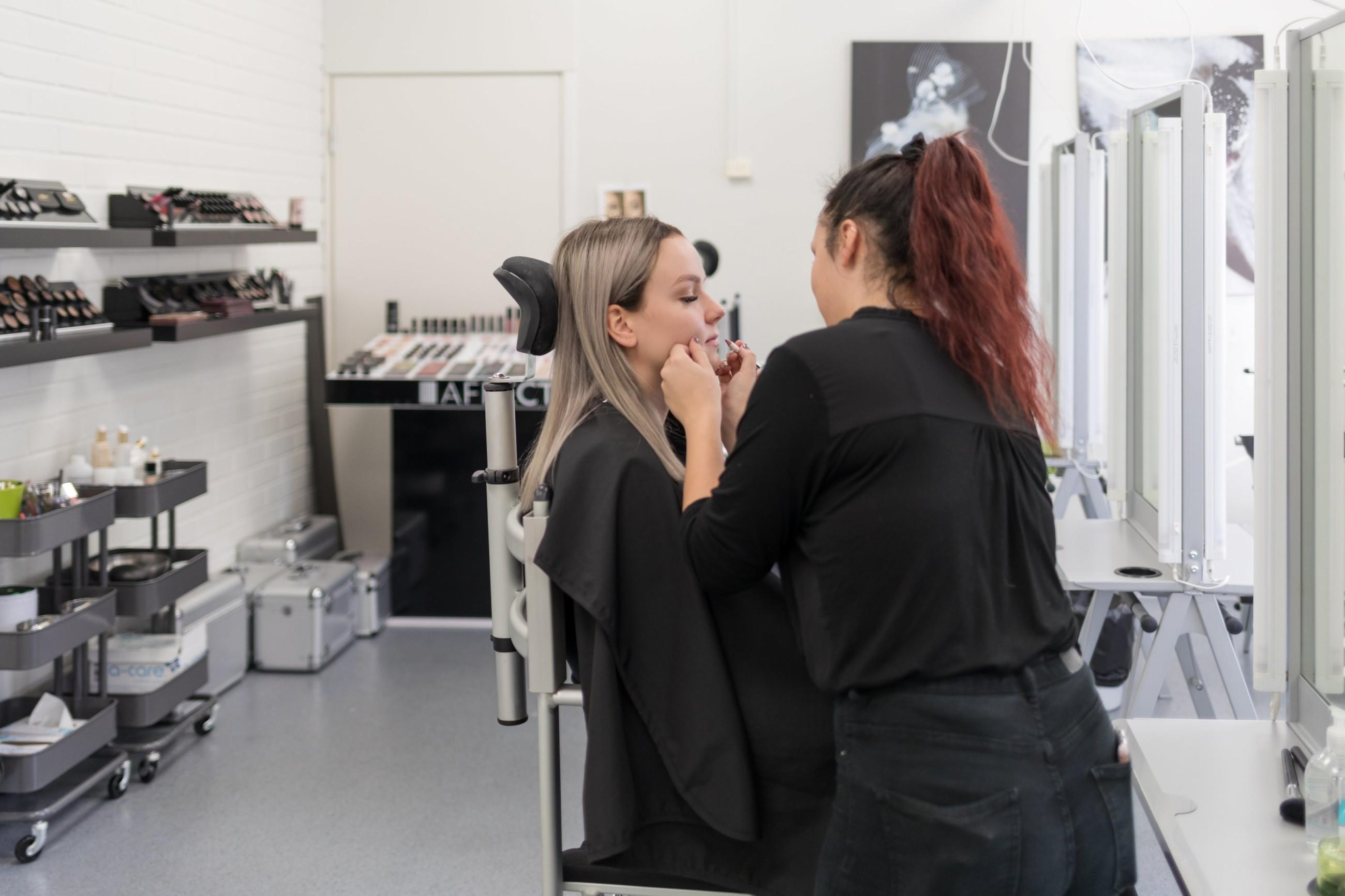 Nainen meikkaa toista naista, taustalla näkyy huone, jonka hyllyillä on kosmetiikkatarvikkeita.