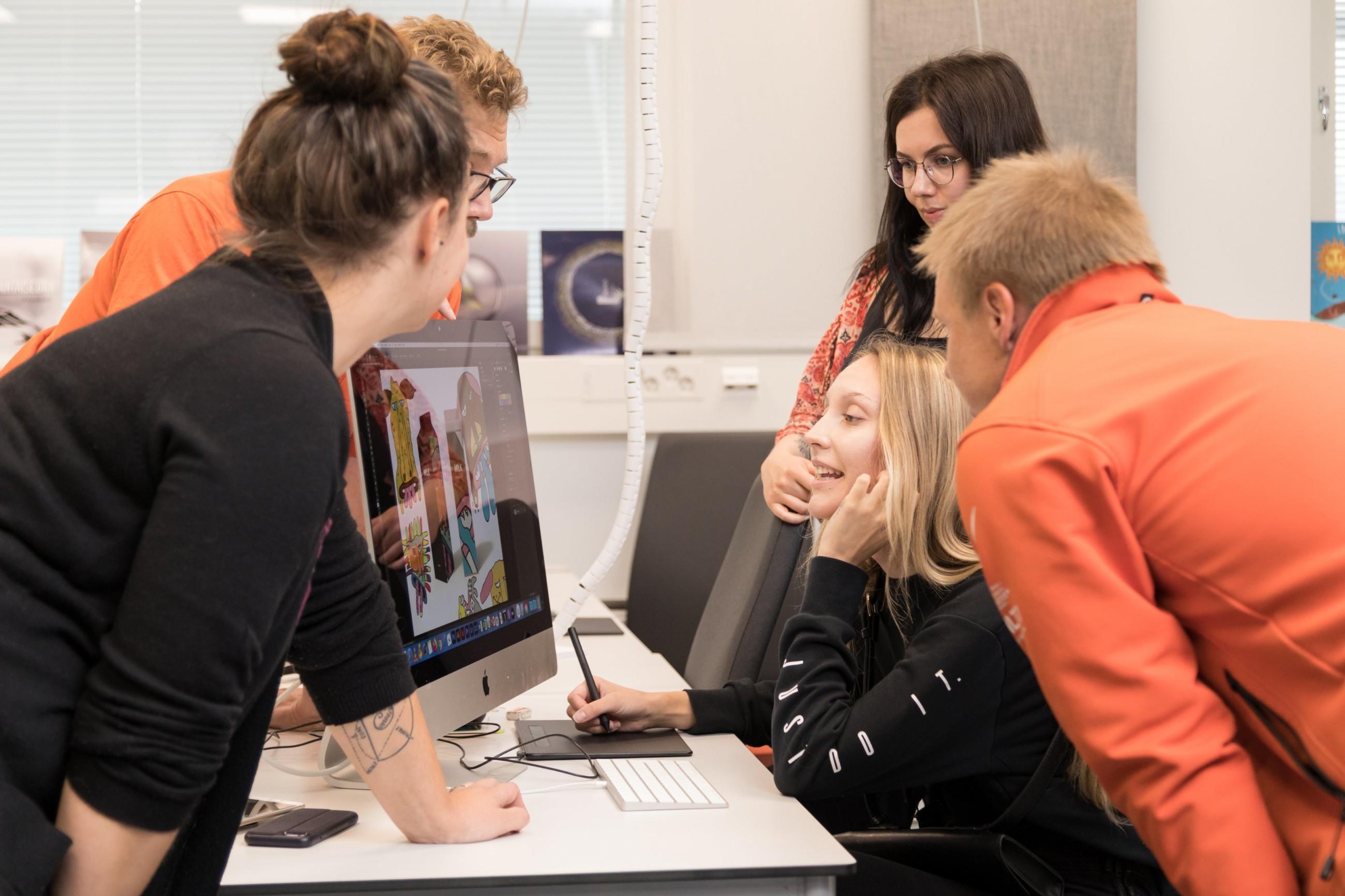 Viisi henkilöä katsoo jotain yhdessä tietokoneen ruudulta