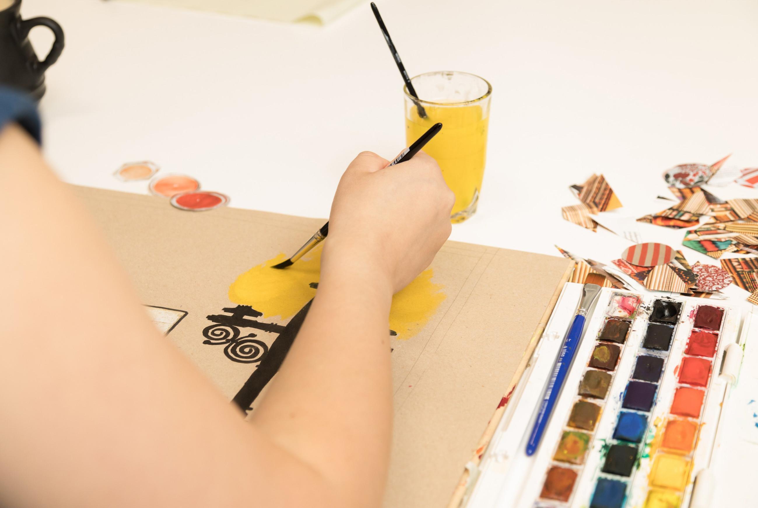 Lähikuva henkilöstä, joka maalaa siveltimellä teosta, pöydällä myös vesiväripaletti.