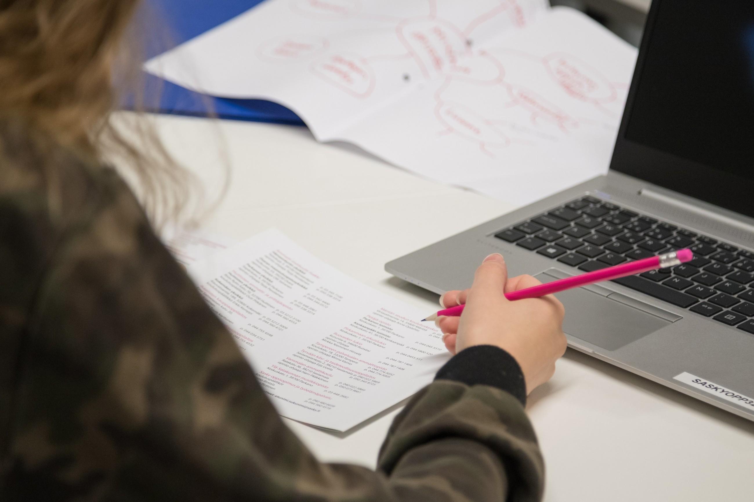 Pöydällä tietokone ja kirjoitusvälineitä.