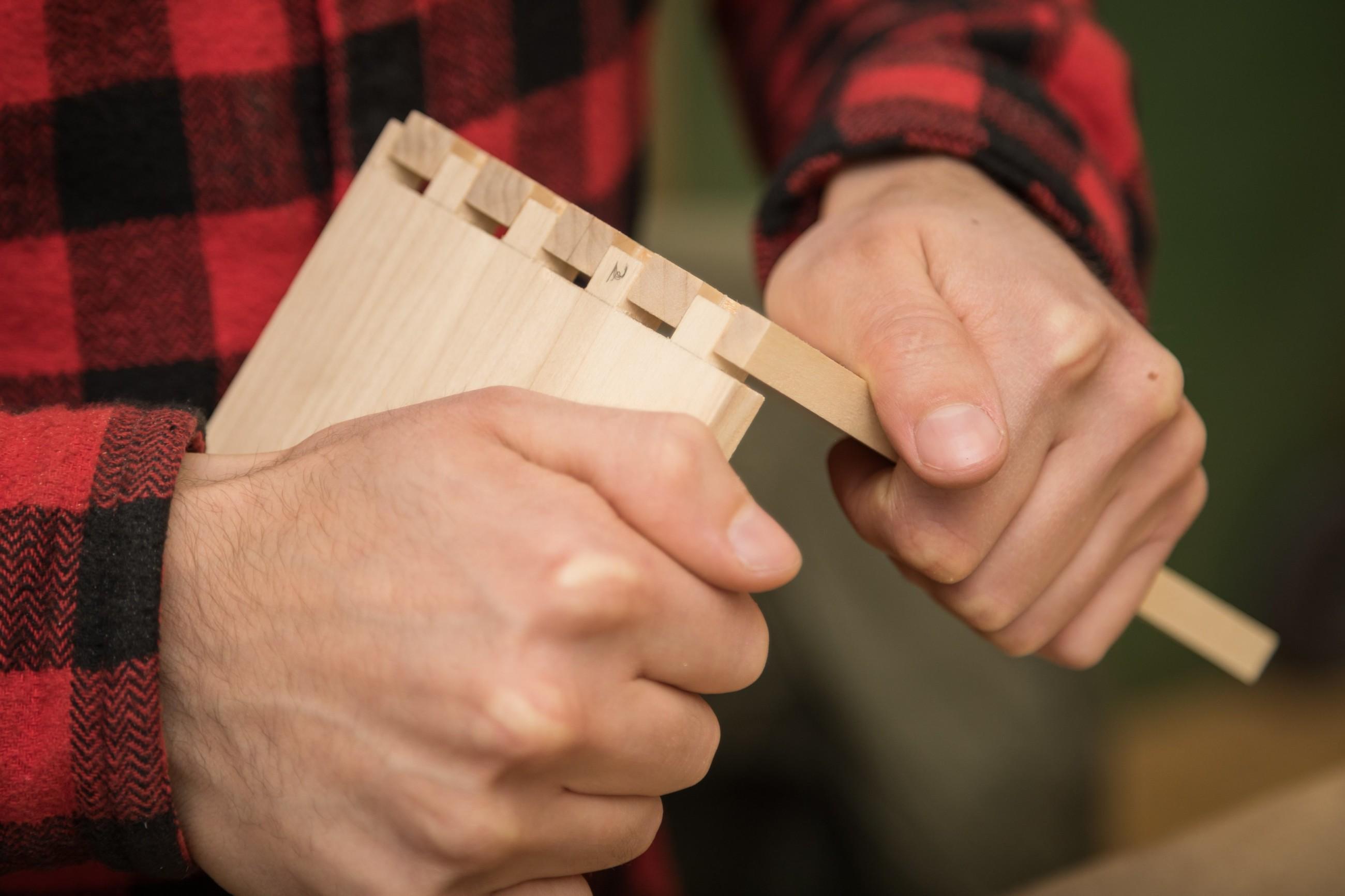 Lähikuva henkilön käsistä ja puuliitoksesta.