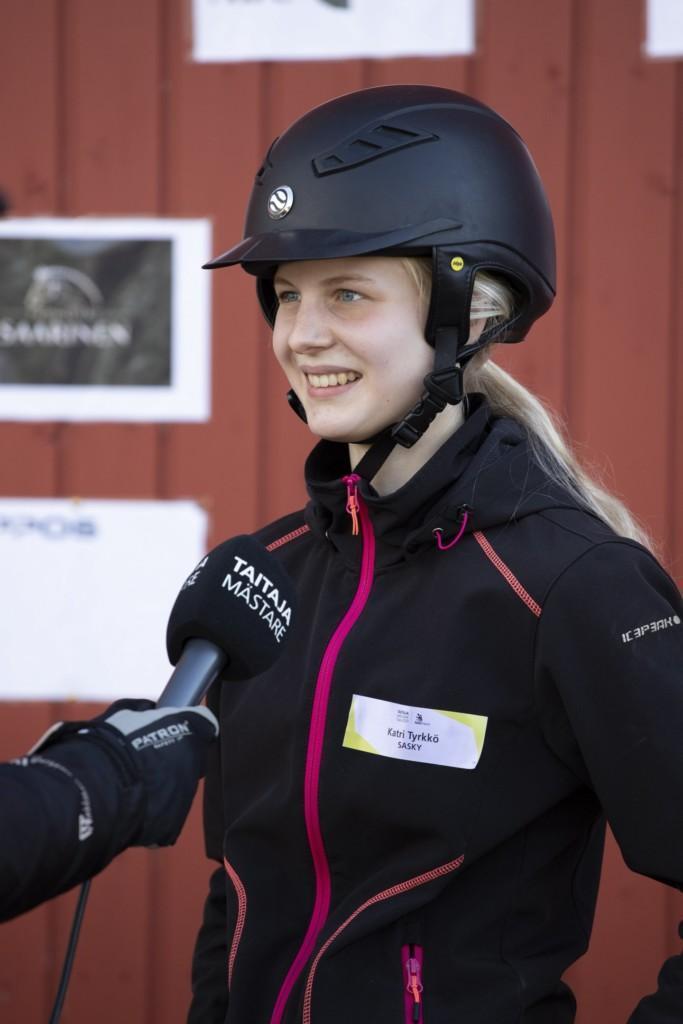 Tyttö ratsastuskypäräpäässään antaa haastattelua hänen edessään olevaan mikrofoniin.