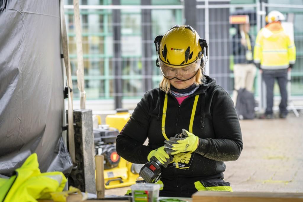 Nainen työvaatteissa, suojakypärä ja suojalasit päässään, akkuporakone kädessään.
