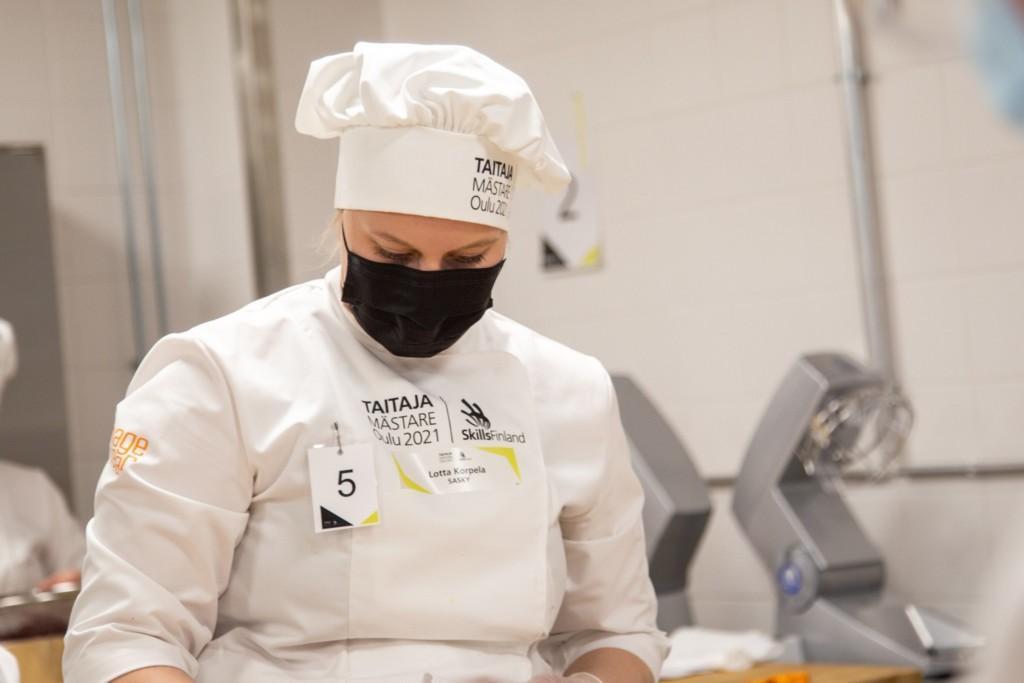 Leipuri työvaatteissan suorittamassa tehtävää.