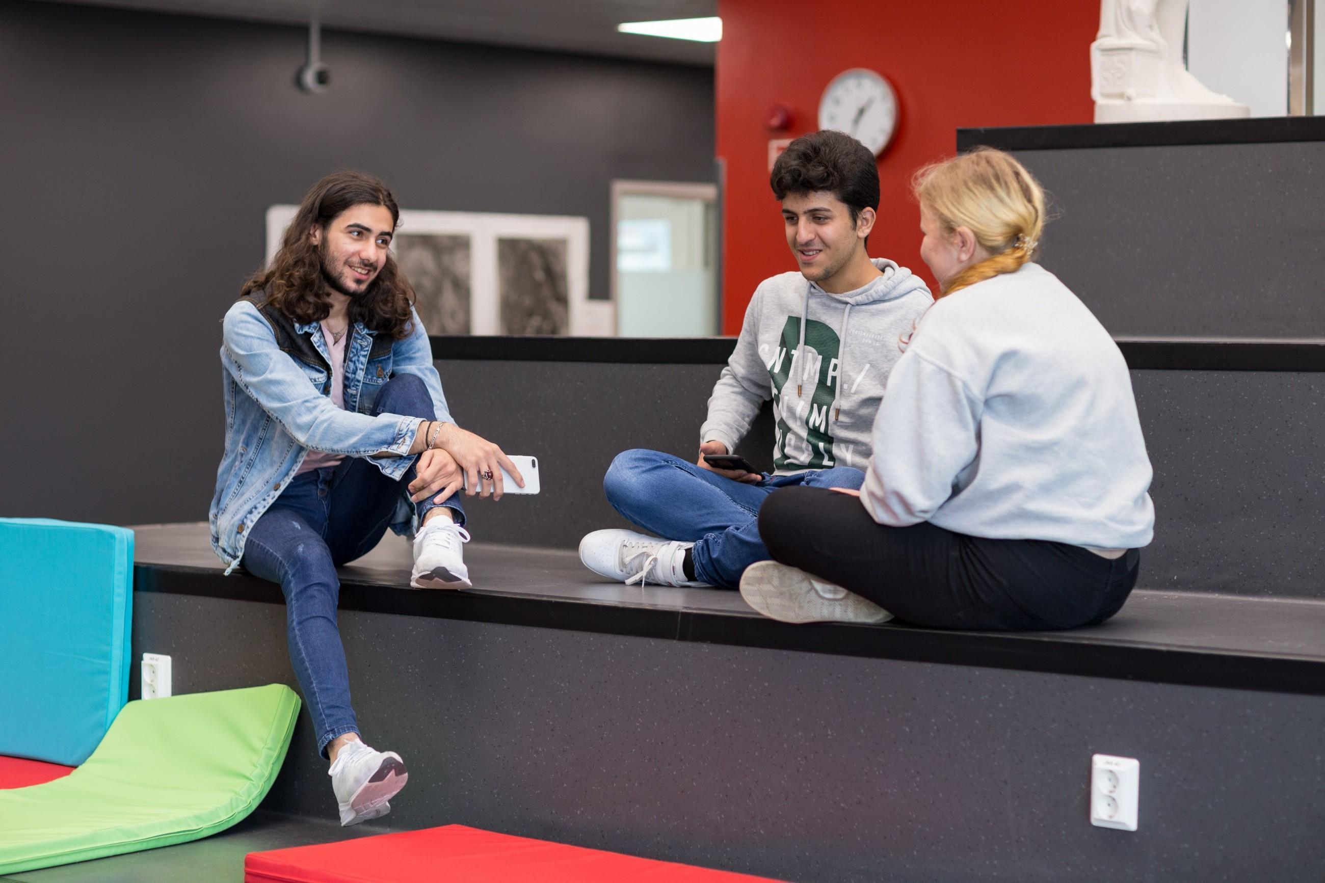 Kolme opiskelijaa istuu portailla sisätiloissa.