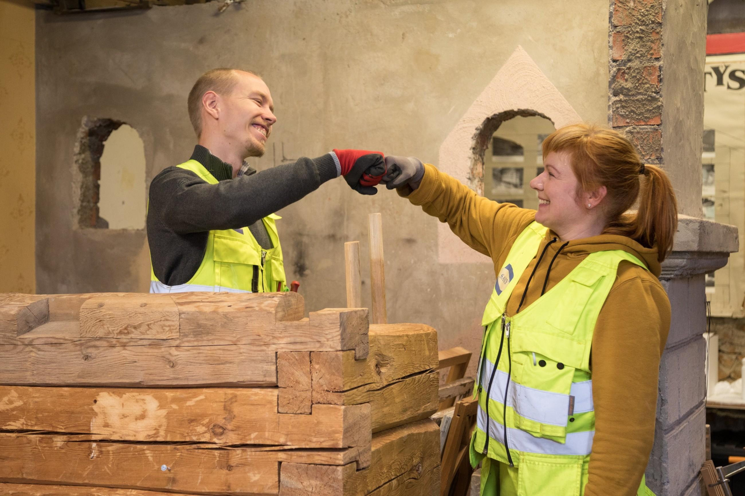 Kaksi henkilöä työhaalareissa tervehtii toisiaan ja hymyilevät, kuvassa henkilöiden välissä hirsirakennelma.