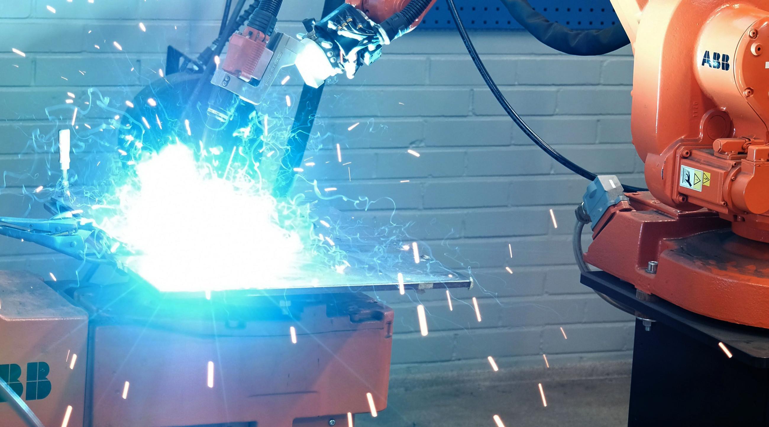 Hitausrobotti työssään, sinistä hitsausvaloa ja hitsauksesta syntyviä kipinöitä.